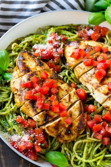 This chicken pesto pasta is a skillet of spaghetti tossed in pesto sauce, topped with grilled chicken strips, fresh tomatoes and basil.