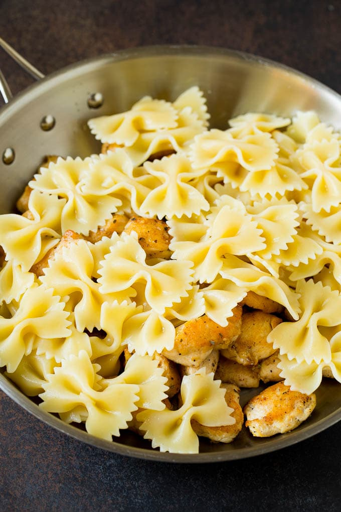 Chicken and farfalle pasta in a pan.