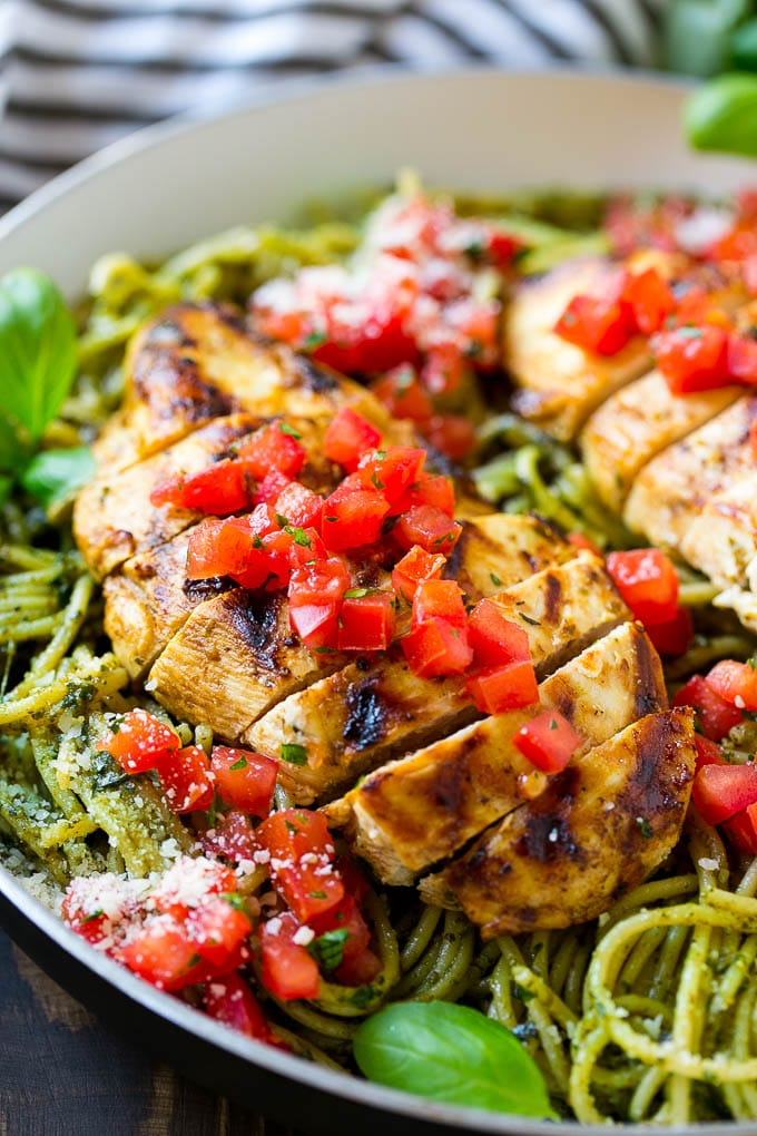 Pesto pasta topped with sliced cooked chicken and fresh tomatoes.