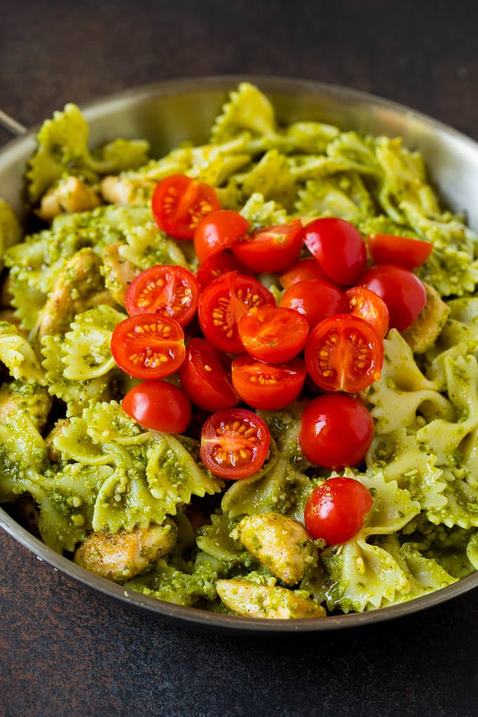 Chicken and pasta topped with cherry tomatoes.