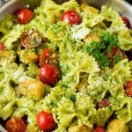 Chicken pesto pasta with cherry tomatoes and parmesan cheese.