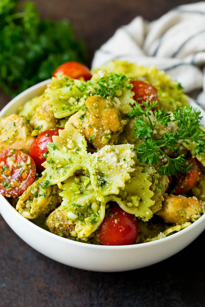 A bowl of chicken pesto pasta garnished with parsley.
