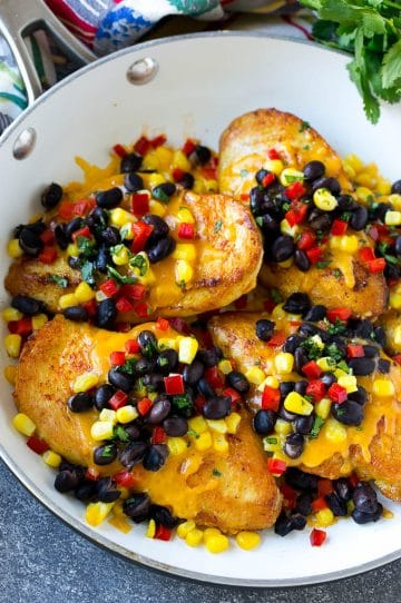 A skillet of chicken Santa Fe which is chicken breasts topped with melted cheddar, black beans, corn and red bell peppers.