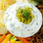 A bowl of dill pickle dip topped with chopped pickles and surrounded by vegetables, pretzels and potato chips.
