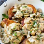 Mushroom pork chops in a skillet topped with creamy mushroom sauce and chopped parsley.