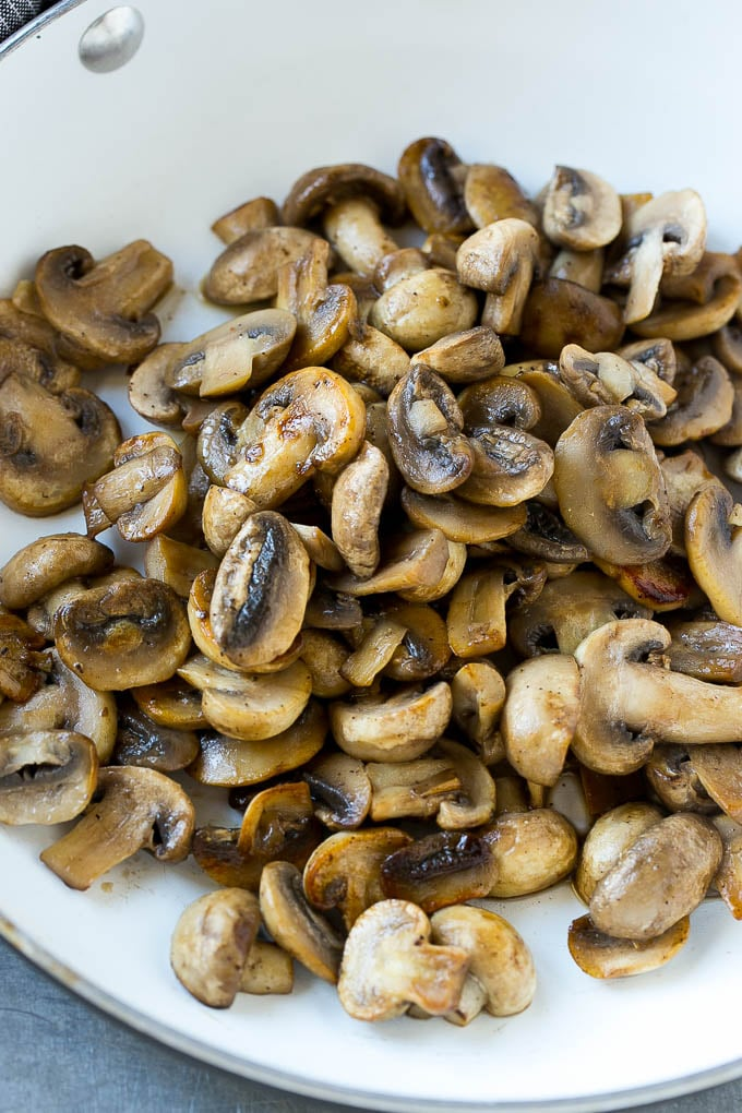 A pan of sauteed mushrooms form the base of mushroom sauce for pork chops.