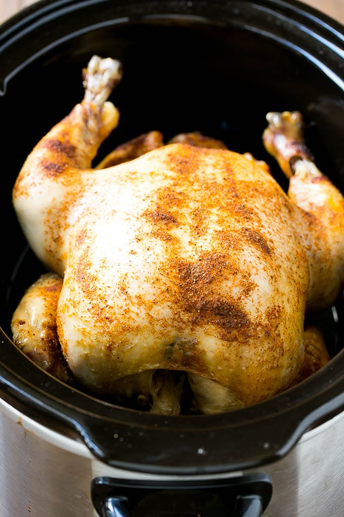A cooked whole chicken in a slow cooker.