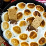 A skillet of s'mores dip with melted milk chocolate topped with toasted marshmallows.