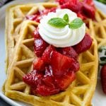 Strawberry waffles are homemade waffles topped with fresh strawberry sauce and whipped cream.