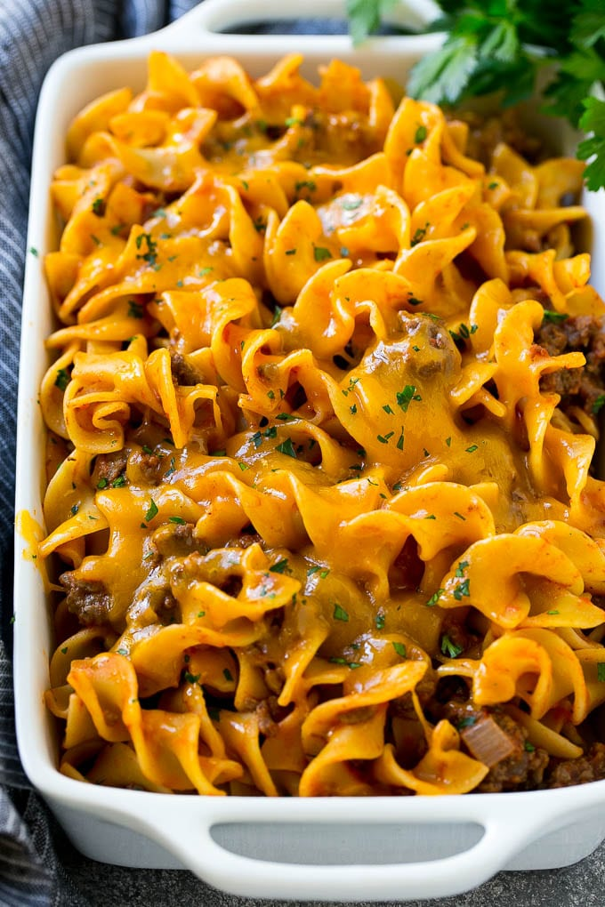Beef noodle casserole in a serving dish topped with melted cheddar cheese and parsley.