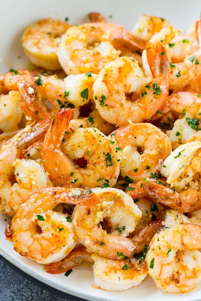 A skillet of shrimp in garlic butter sauce, garnished with parsley.