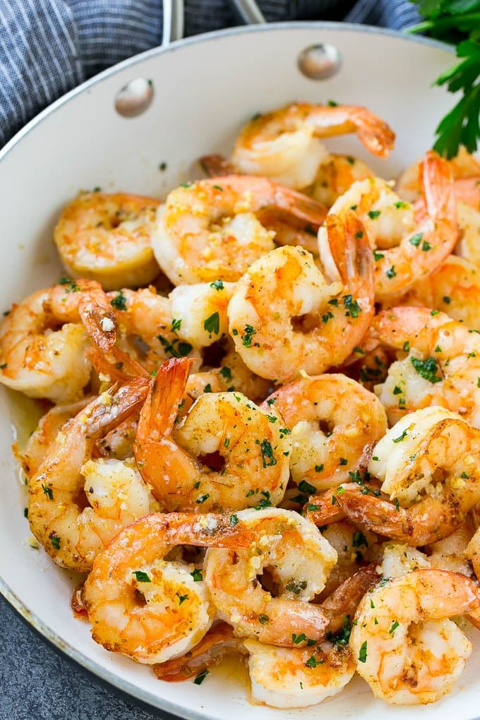 Shrimp in a skillet that are seared in garlic butter and sprinkled with parsley.