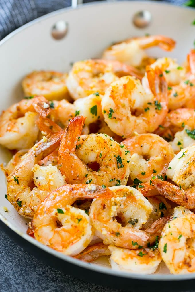 A pan of garlic butter shrimp in a savory sauce, finished off with chopped parsley.