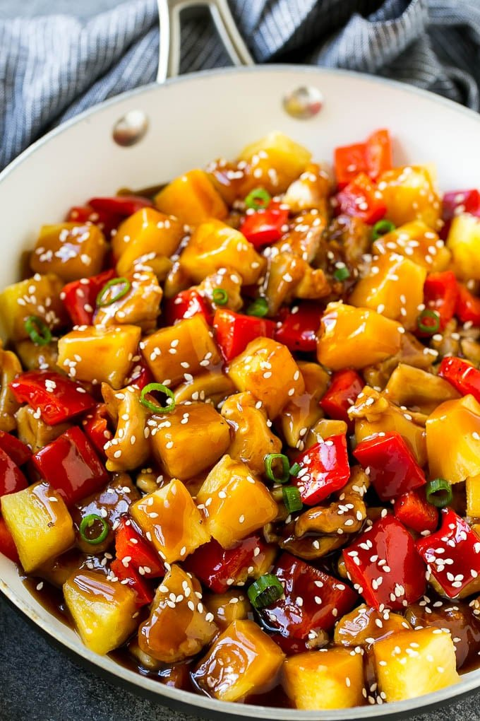 Pineapple chicken stir fry in a skillet, topped with sauce, sesame seeds and green onions.