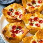 A plate of pizza muffins made with crescent roll dough, pizza sauce, melted cheese and mini pepperoni.