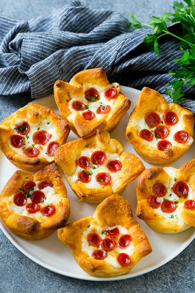 Pizza muffins on a serving plate garnished with parsley.