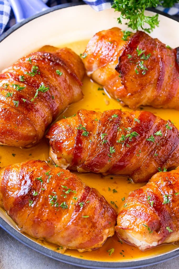 A pan of bacon wrapped chicken baked to golden brown and topped with parsley.