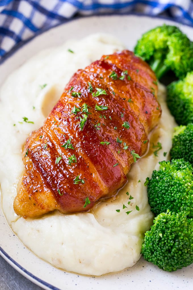 Bacon wrapped chicken served over mashed potatoes with broccoli on the side.