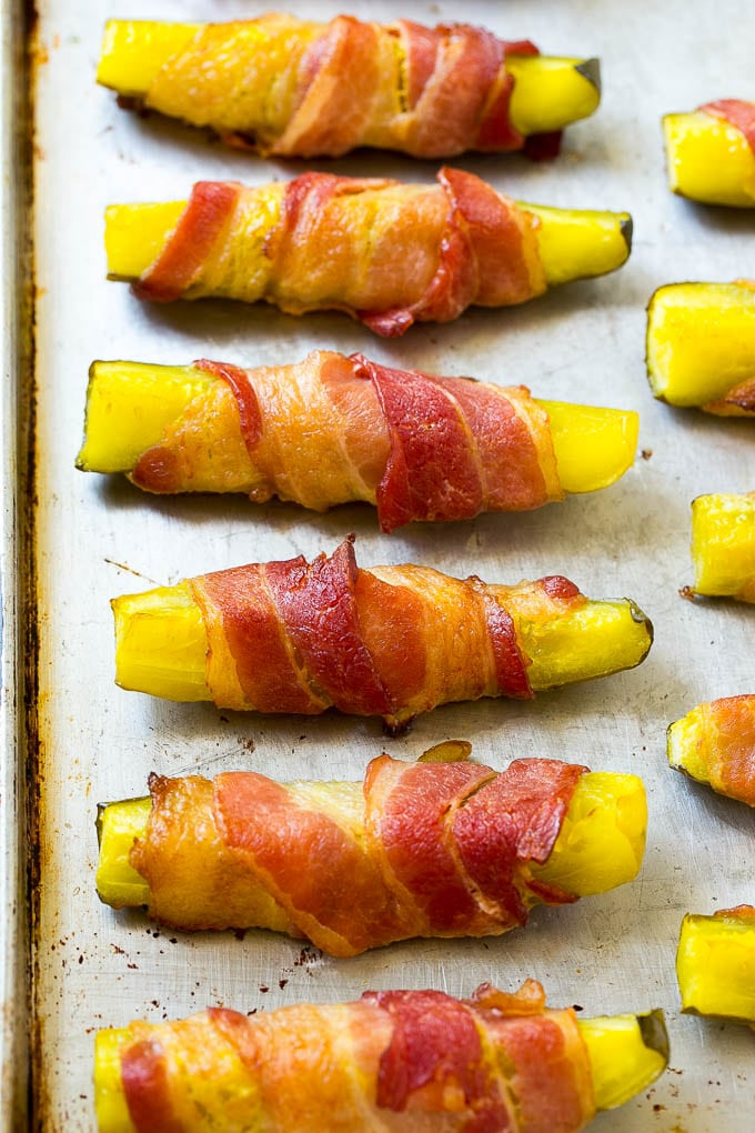Crispy bacon wrapped pickle spears on a sheet pan.