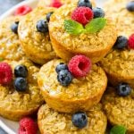Baked oatmeal cups on a platter topped with maple syrup, berries and mint.