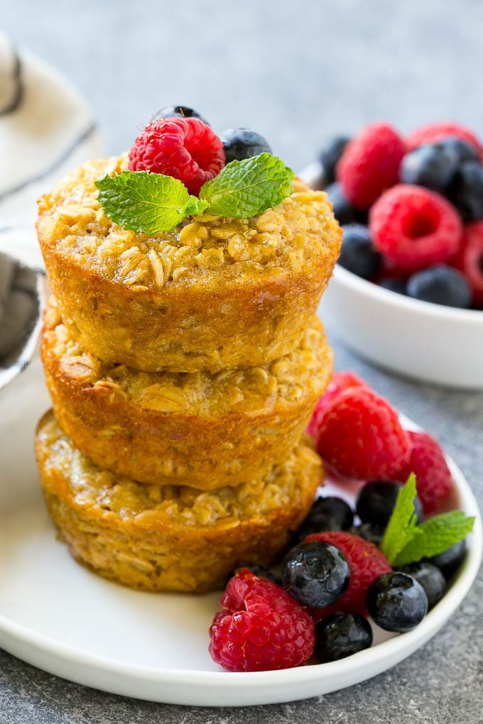 A stack of baked oatmeal cups topped with syrup, raspberries, blueberries and mint.