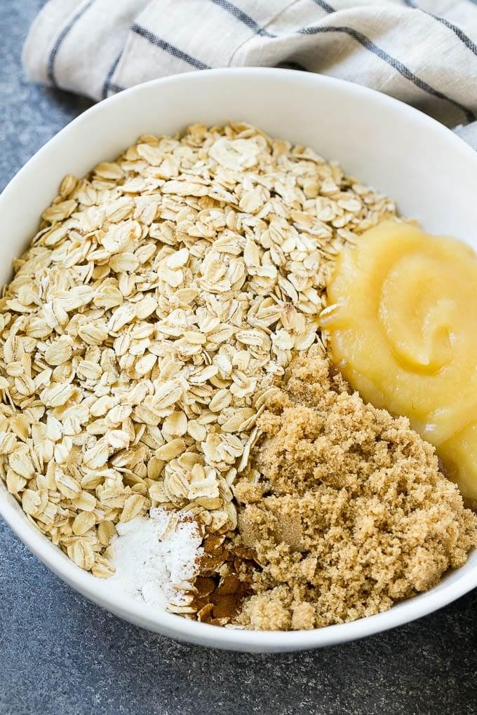 A bowl of oats, applesauce, brown sugar, cinnamon and baking powder.
