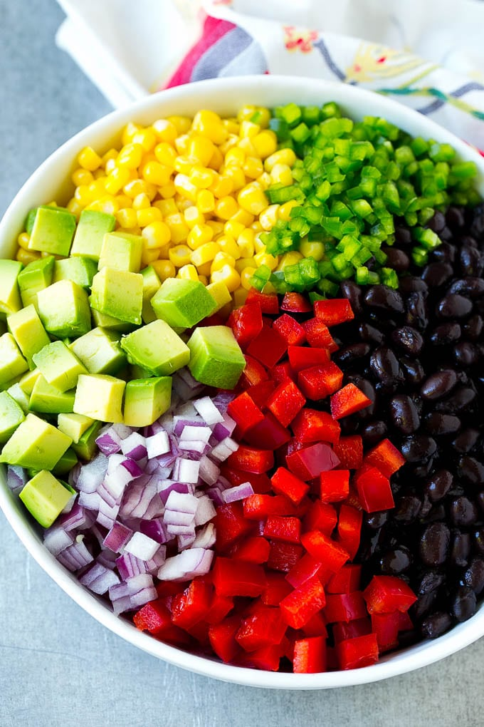 A bowl of black beans, corn, diced red peppers, minced jalapeno, red onion and avocado.