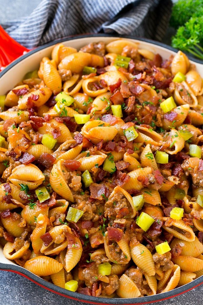 Cheeseburger pasta in a skillet topped with pickles and bacon.