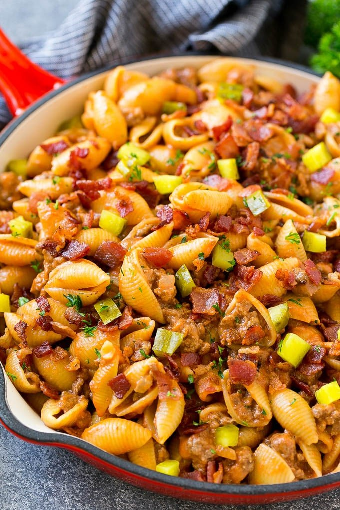 A pan of pasta with ground beef, onion, pasta shells, cheddar cheese and bacon.