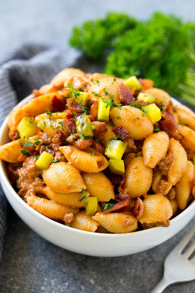 A bowl of cheeseburger pasta topped with bacon and chopped pickles.
