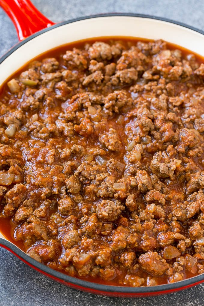 Ground beef, onions and tomato sauce in a skillet