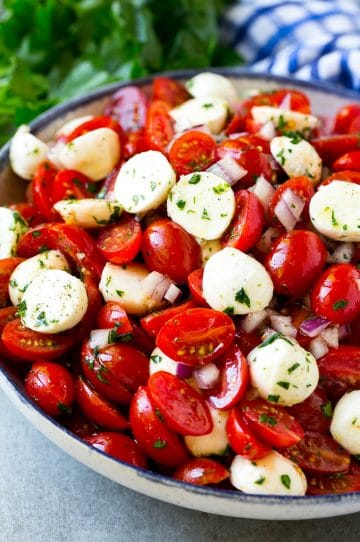 Cherry tomato salad with halved cherry tomatoes, mozzarella balls and red onion, all tossed with herbs and dressing.