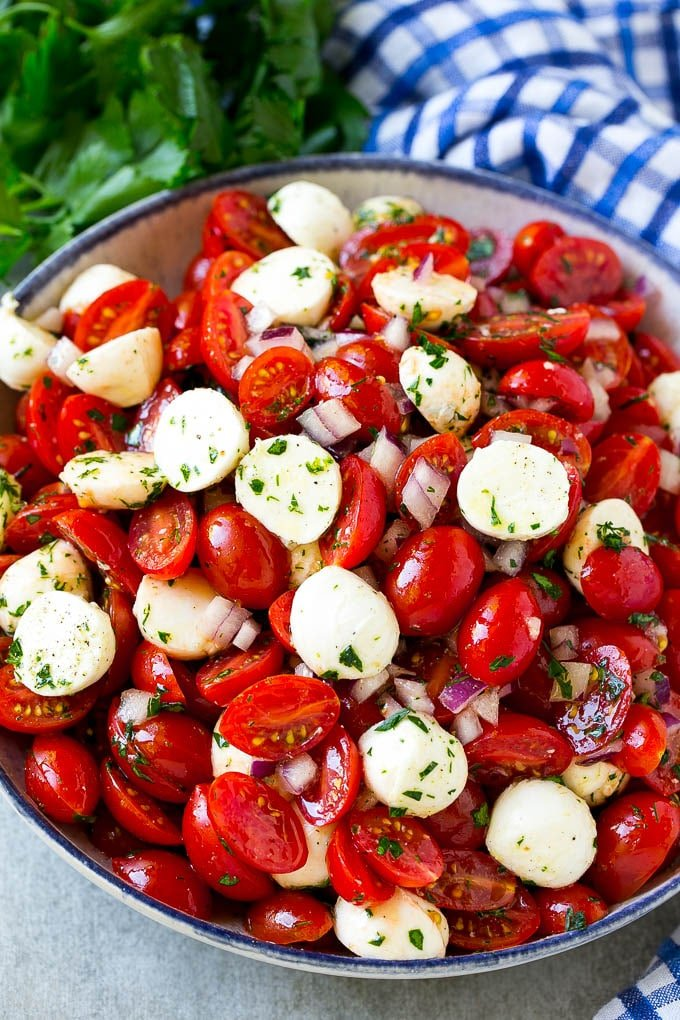 A serving bowl of tomato mozzarella salad with cherry tomatoes, herbs and red onion.