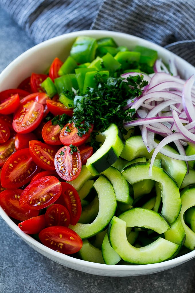 A bowl of sliced cucumber, halved tomatoes, green bell pepper, parsley and sliced red onion.