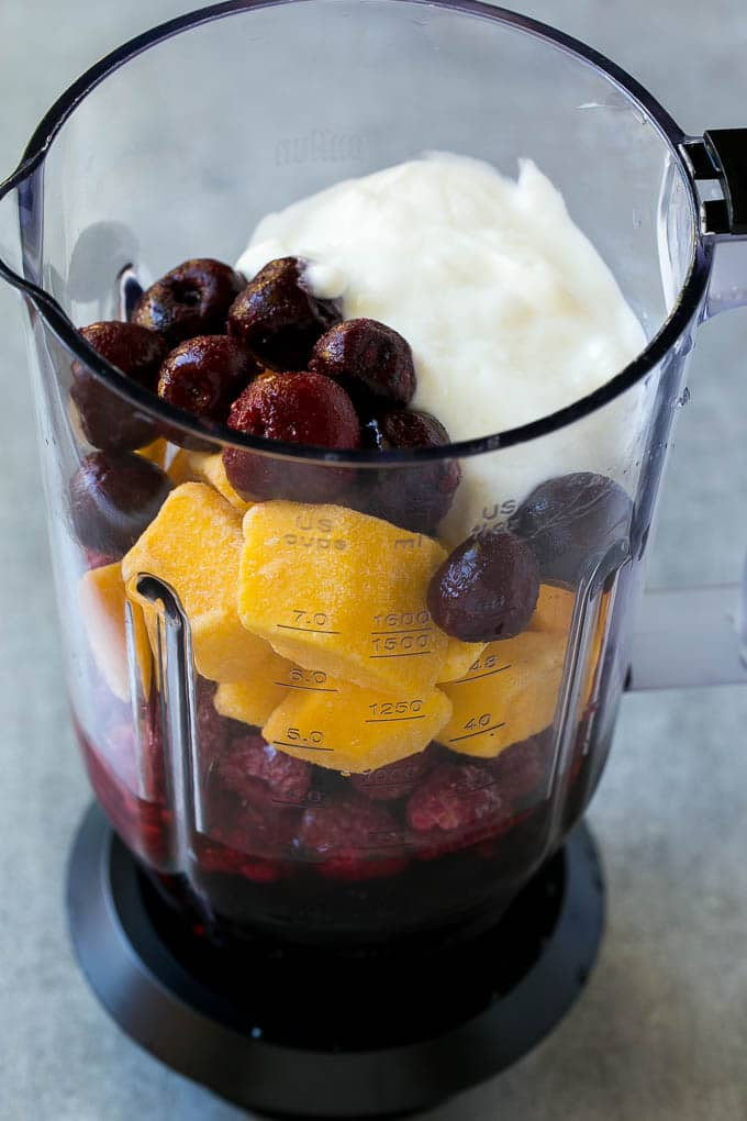 A blender full of frozen fruit, juice and yogurt.