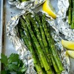 Grilled asparagus in foil topped with parsley and seasonings.