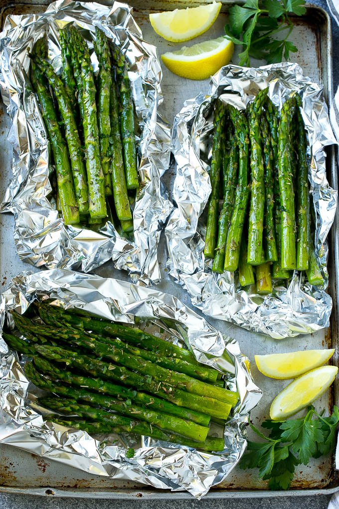 Grilled asparagus in foil on a sheet pan with lemon wedges and parsley.