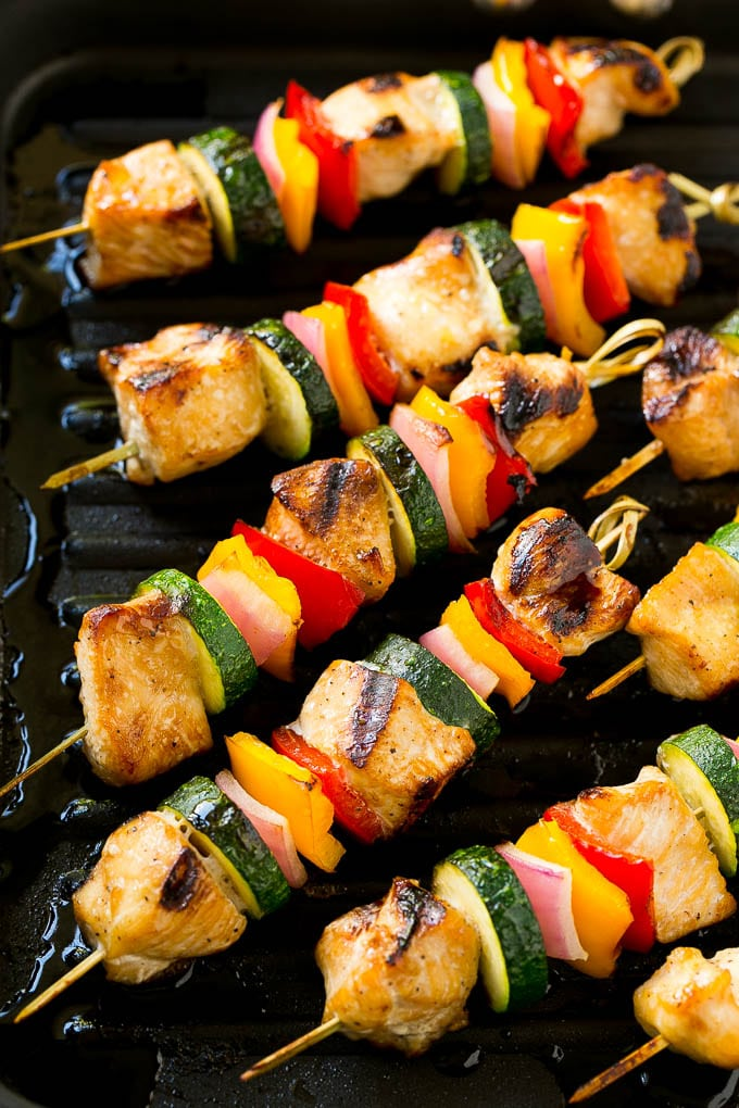 Cooked grilled chicken kabobs on a grill pan.