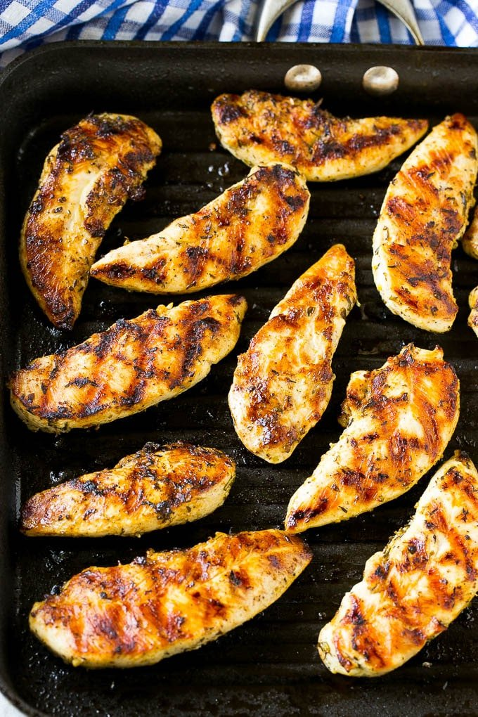 Chicken tenders cooking on a grill pan.