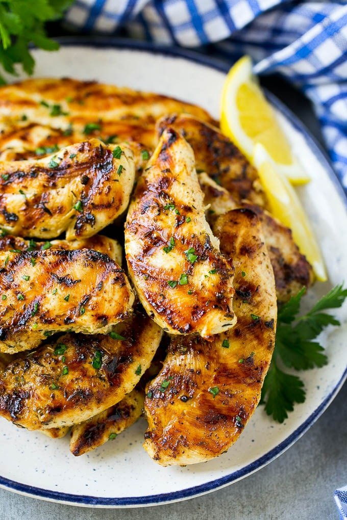 A pile of grilled chicken tenders topped with fresh herbs and garnished with lemon wedges.