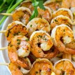 Grilled shrimp skewers with lemon wedges and parsley.