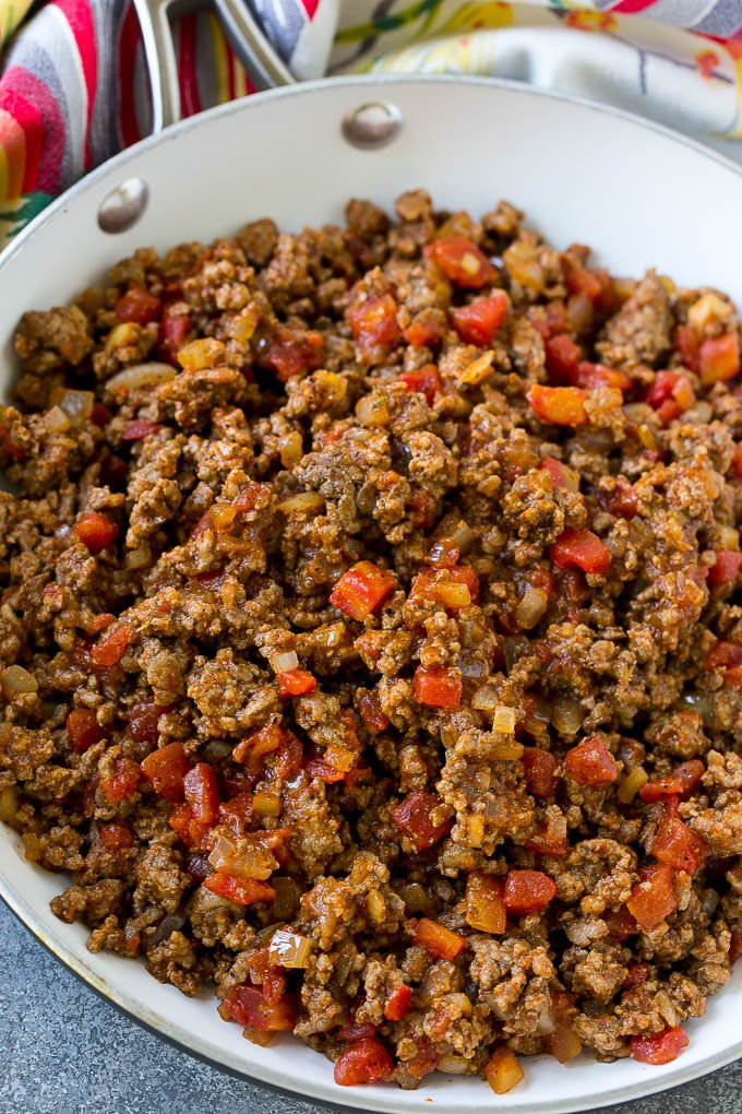 A skillet of ground beef cooked with taco seasoning, onions and tomatoes.