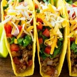 Ground beef tacos in hard taco shells topped with shredded cheese, lettuce, tomato and onion.