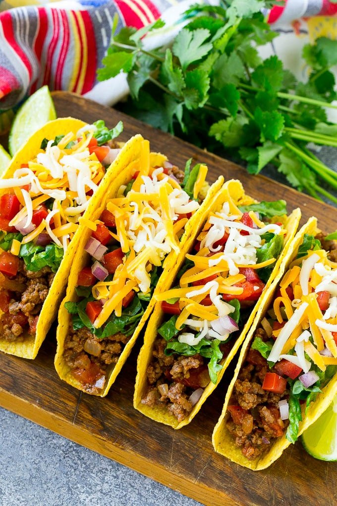 Crispy ground beef tacos with an assortment of toppings like lettuce, tomato and shredded cheese.