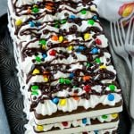 An ice cream sandwich cake with layers of the sandwiches, whipped topping and chocolate candy.