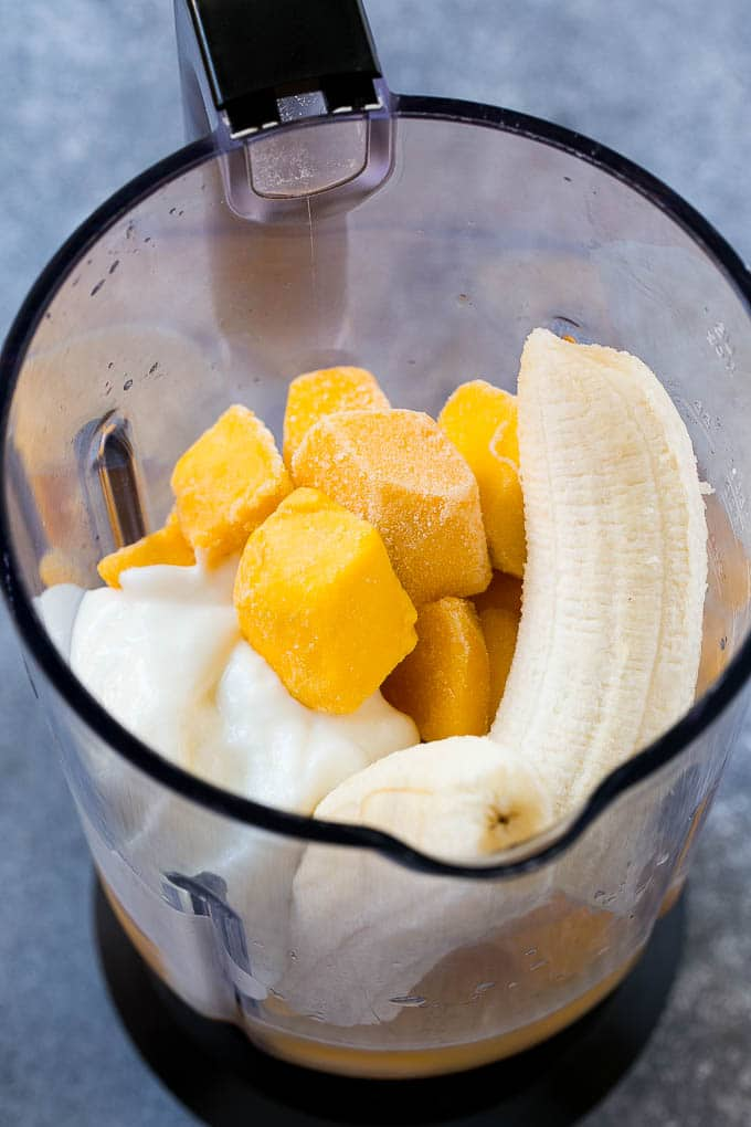 Frozen mango, banana, yogurt and juice in a blender.