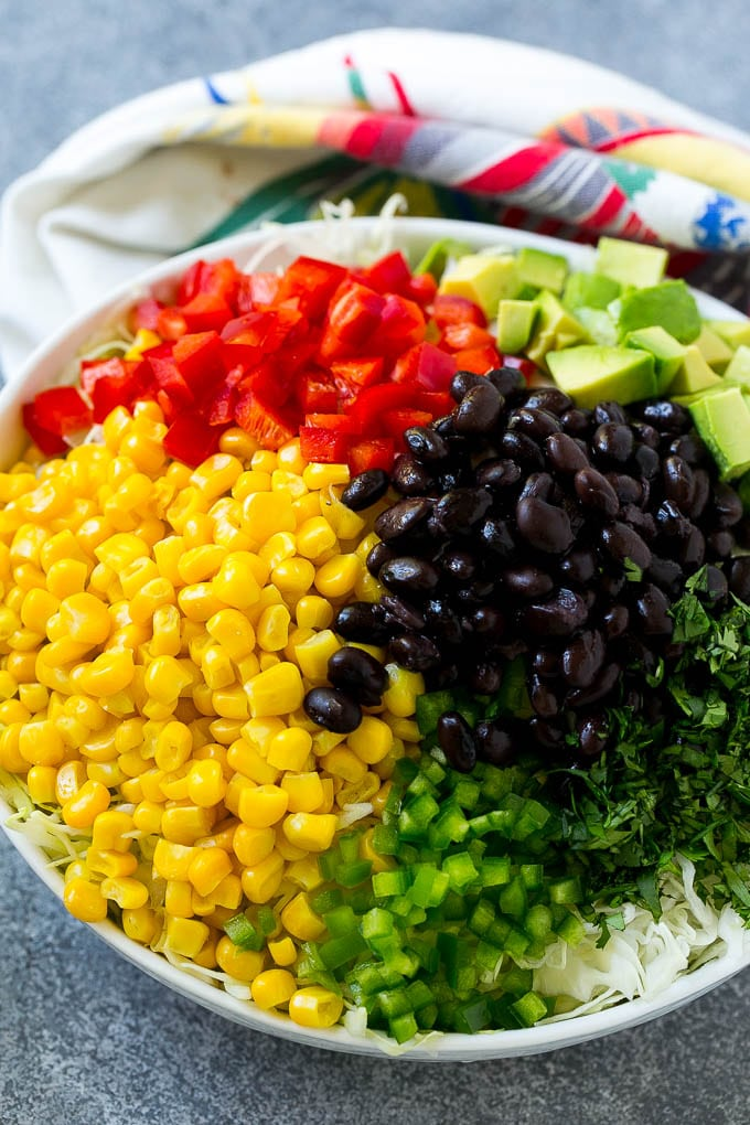 A bowl of shredded cabbage, corn, black beans, red peppers, jalapeno and avocado.