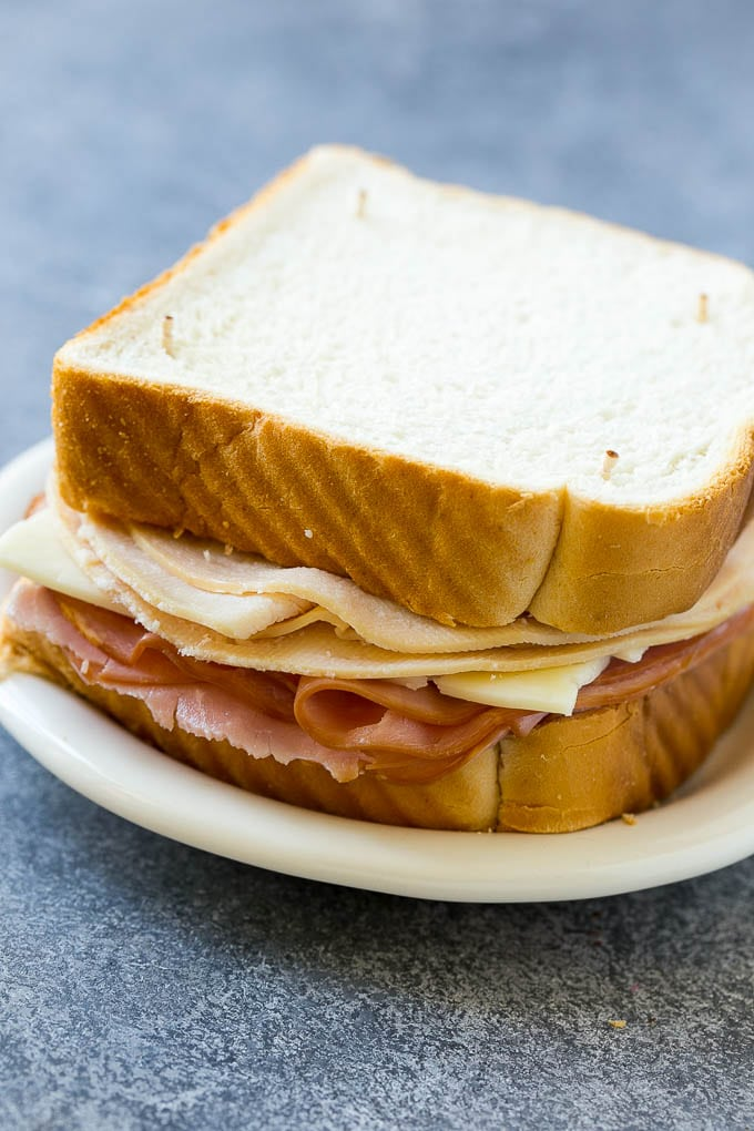 An uncooked Monte Cristo sandwich with bread, ham, turkey and cheese.