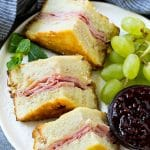 A plate of Monte Cristo sandwich with fresh fruit and raspberry jam for dipping.