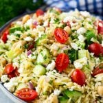 Orzo salad in a serving bowl with tomatoes, cucumbers and chickpeas.